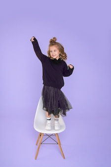 Beautiful funny girl 6-7 years old is dancing on chair in studio on violet background. concept of joy of victory, surprise. full length photo