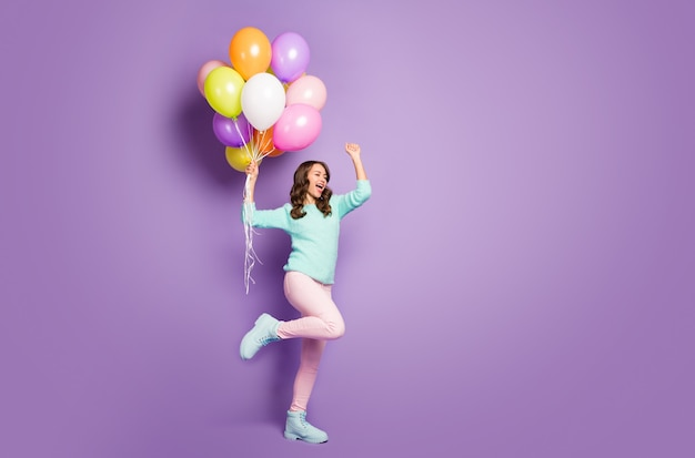 Beautiful funny lady hold many colorful air balloons celebrate party start wear fuzzy sweater pink pants pastel shoes.