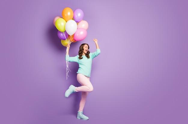 美しいおかしい女性は多くのカラフルな風船を持ってパーティーを祝うファジーセーターピンクパンツパステルシューズを着用してください。