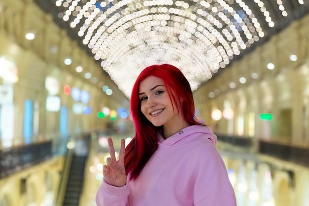 明るい街の通りで夕方にピンクのパーカーで美しい面白い赤毛の10代の少女。