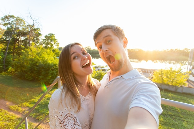 Beautiful funny romantic couple on nature background. attractive young woman and handsome man are making selfie, smiling and looking at camera.