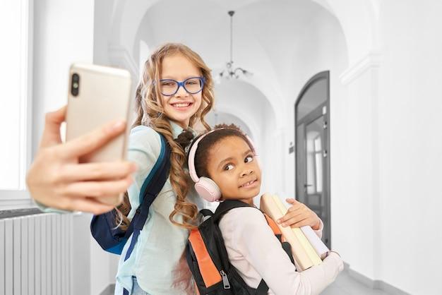Beautiful, funny school friends doing selfie in school hallway on phone.