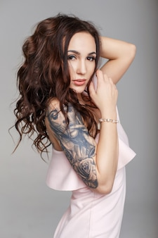 회색 배경에 분홍색 이브닝 드레스에 그녀의 팔에 문신과 머리를 가진 아름다운 재미있는 여자