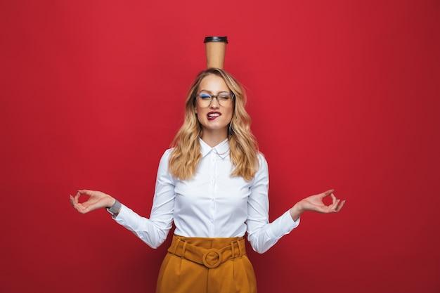 Красивая смешная молодая блондинка женщина, стоящая изолирована на красном фоне, балансируя, держа чашку кофе