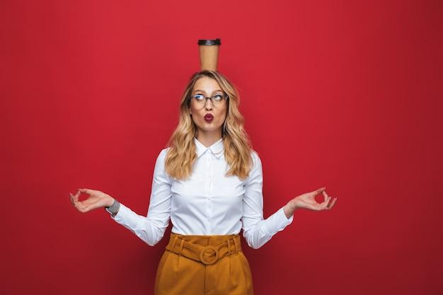 아름 다운 재미 젊은 금발의 여자 빨간색 배경 위에 절연 서, 균형, 커피 컵을 들고