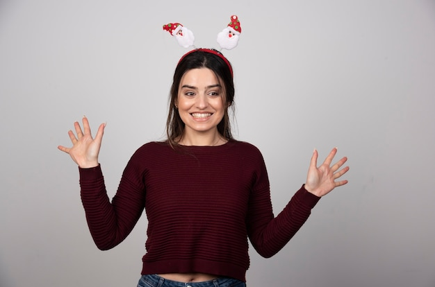 Beautiful funny young woman in christmas headband over isolated gray background.
