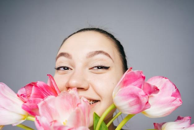 아름 다운 재미 있는 젊은 여자 웃 고 웃 고, 분홍색 향기로운 꽃의 꽃다발을 들고