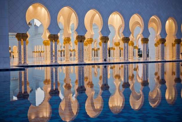 アラブ首長国連邦のアブダビにある有名なシェイクザイードホワイトモスクの美しいギャラリー。日没時の反射