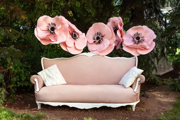 夏の日の美しい庭のヴィンテージピンクのソファ。インテリアの結婚式の装飾。春の庭に大きな花で飾られたクラシックなソファ。屋外でリラックスできるガゼボ。ロマンチックな床の間。大きな紙の花。