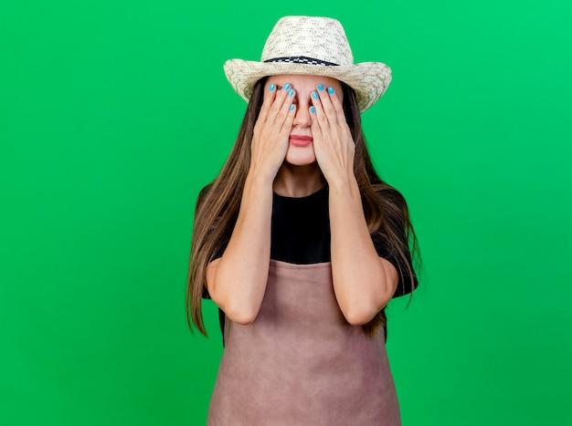 Красивая девушка садовник в униформе в садовой шляпе, покрытой руками, глазами, изолированными на зеленом