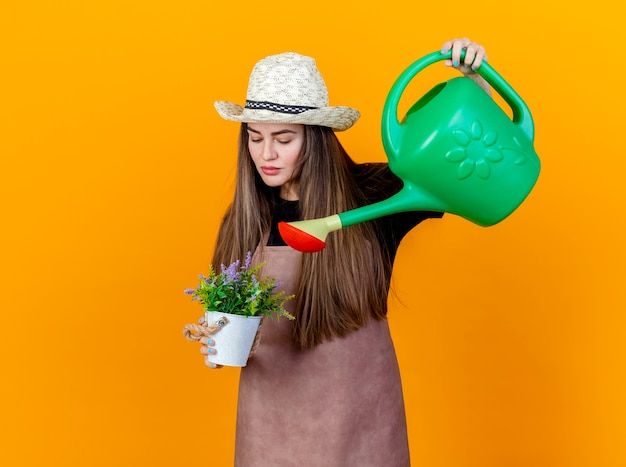 Beautiful gardener girl wearing uniform and gardening hat watering flower in flowerpot with watering can isolated on orange background