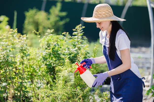 밀 짚 모자에 아름 다운 정원사 여자는 정원 분무기에서 식물을 뿌린다.