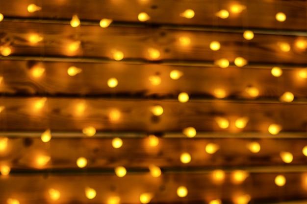 Beautiful garland hanging on wooden wall, soft focus, bokeh, luminous christmas decor.