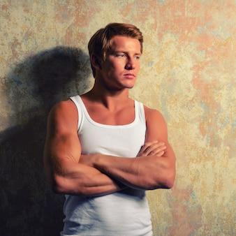グランジ空間に対してポーズをとる白いtシャツの美しいゲイ