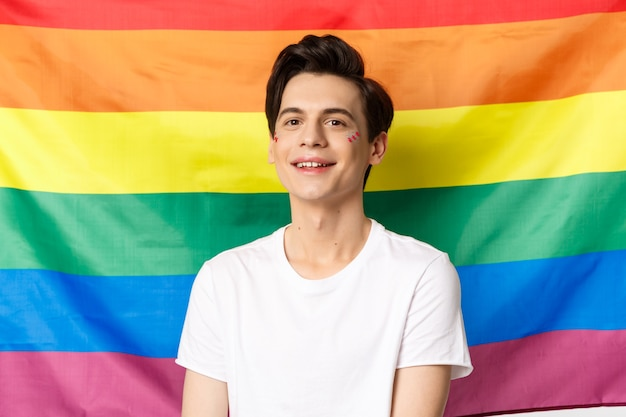 Beautiful gay man with glitter on face, smiling happy and proud at camera, standing against rainbow pride flag, lgbtq community rights and people concept.