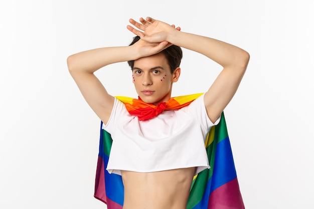 Beautiful gay man with glitter on face, wearing crop top and rainbow lgbt flag, posing against white background.