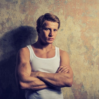 Beautiful  gay in white t-shirt posing against grunge space