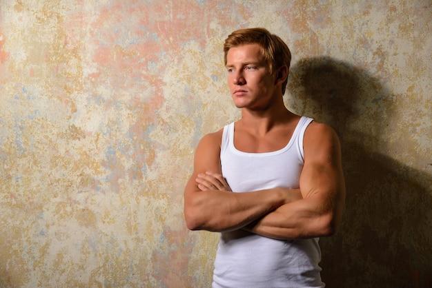 Beautiful  gay in white t-shirt posing against grunge