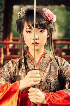 Красивая гейша в кимоно с самурайским мечом