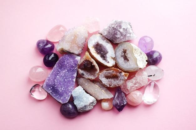ピンクの背景に美しい宝石、ジオードアメジスト、天然紫色のミネラルアメジストの結晶。アメジストとローズクォーツ。半貴石の大きな結晶。