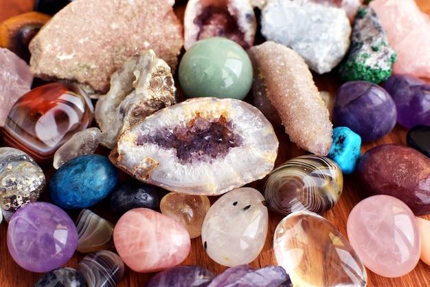 木製の背景に美しい宝石、ジオードアメジスト、天然紫色のミネラルアメジストの結晶。アメジストとローズクォーツ。半貴石の大きな結晶。