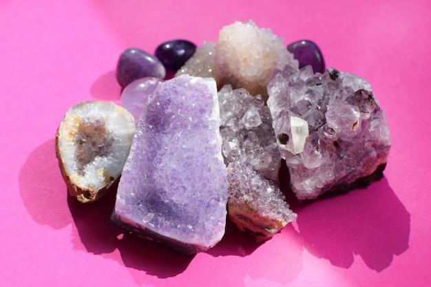 明るいピンクの背景に美しい宝石、アメジストのジオード、天然紫のミネラルアメジストの結晶。アメジストとローズクォーツ。半貴石の大きな結晶。