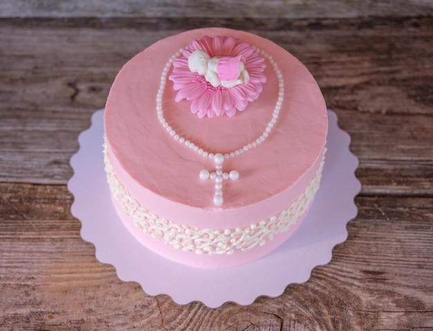 子供の洗礼の際に赤ちゃんの姿と十字架が付いた美しい優しいピンクのケーキ