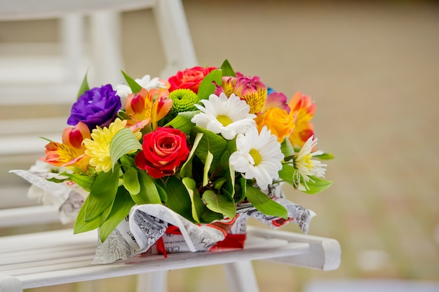 Beautiful gift bouquet in a wooden vase on a wooden bench.