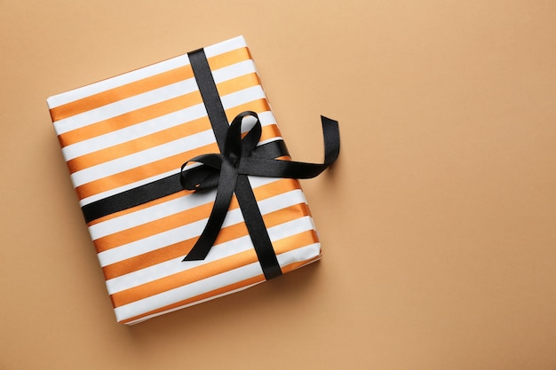 Красивая подарочная коробка на цветной поверхности