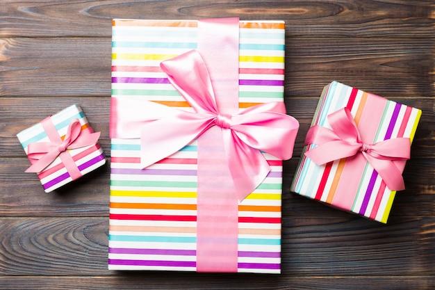 Красивая подарочная коробка с цветным бантом на темном деревянном столе. вид сверху с копией пространства для вашего дизайна. рождественское понятие.
