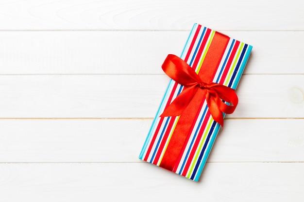 흰색 나무 테이블에 색색의 활이 있는 아름다운 선물 상자. 디자인을 위한 복사 공간이 있는 상위 뷰 배너입니다.