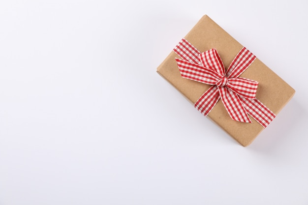 Beautiful gift box with checkered bow on white background, space for text