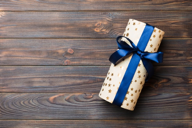 Beautiful gift box with a colored bow on the dark wooden table