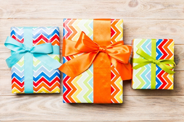 Beautiful gift box with a colored bow on the orange wooden table