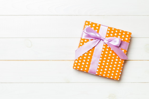 Beautiful gift box with a colored bow on the white wooden table