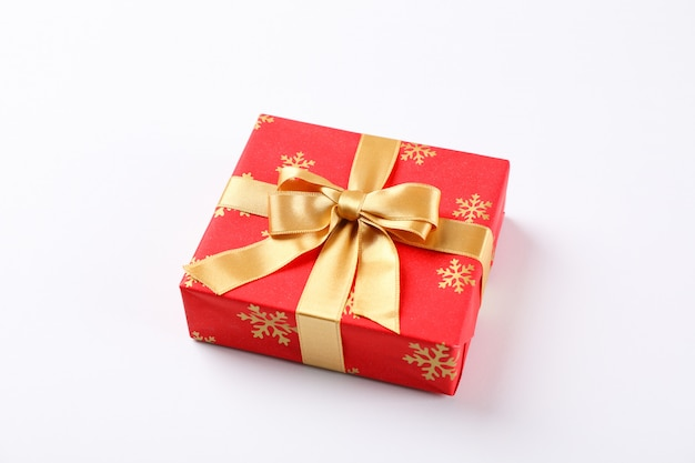 Beautiful gift box with golden bow on white background, space for text
