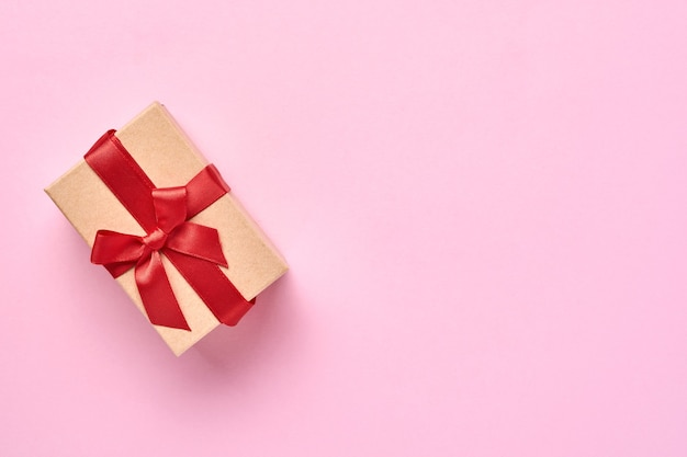 Красивая подарочная коробка с красной лентой на стене розового фона. валентинка.