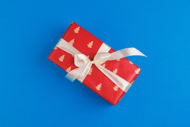 Красивая подарочная коробка, завернутая в праздничную бумагу, с бантом сверху