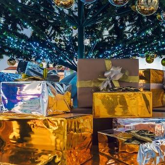 아름다운 선물 상자와 배경에 흐릿한 크리스마스 트리. 나무 아래 바닥에 누워 반짝이는 금색 포장에 담긴 선물. 산타클로스의 선물.
