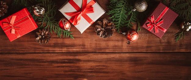 Красивые подарочные коробки, еловые ветки и елочные шары на деревянных фоне. место для текста.