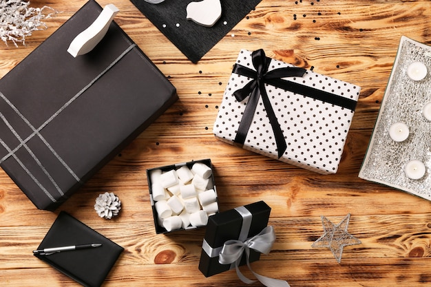 Beautiful gift boxes with decor on wooden background. flat lay composition
