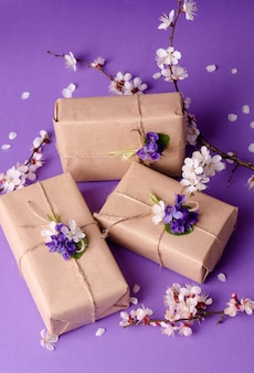 Beautiful gift boxes wrapped in simple brown craft paper decorated with live flowers of violet