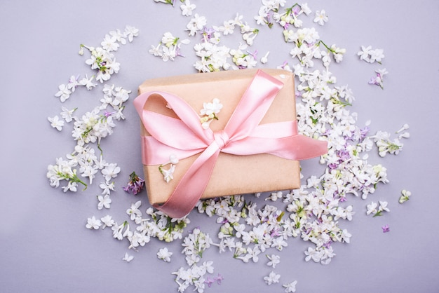 A beautiful gift with a satin ribbon against the background of lilac flowers.