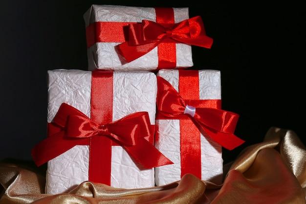 暗い背景に赤いリボンの美しい贈り物