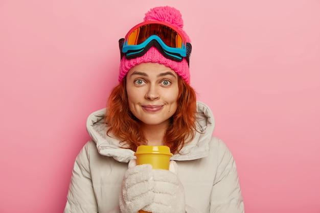 Bella adolescente femminile di zenzero gode di sport estremi, beve caffè dopo lo snowboard, guarda con piacere alla telecamera, indossa occhiali da sci