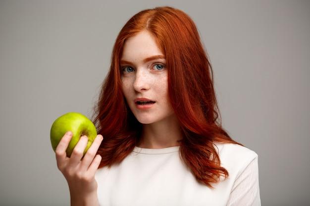 Красивая рыжая девочка держит зеленое яблоко над серой стеной.