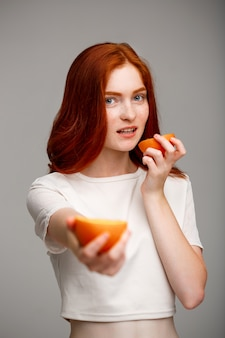 Beautiful ginger girl holding oranges over gray wall.