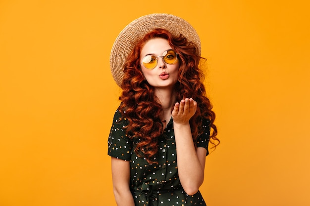 Beautiful ginger girl sending air kiss on yellow background. studio shot of curly young woman in sunglasses and straw hat.
