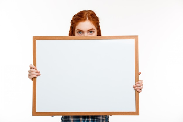 白い壁にホワイトボードを持つ美しい生姜少女。