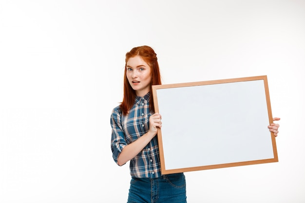 Beautiful ginger girl with whiteboard over white wall.
